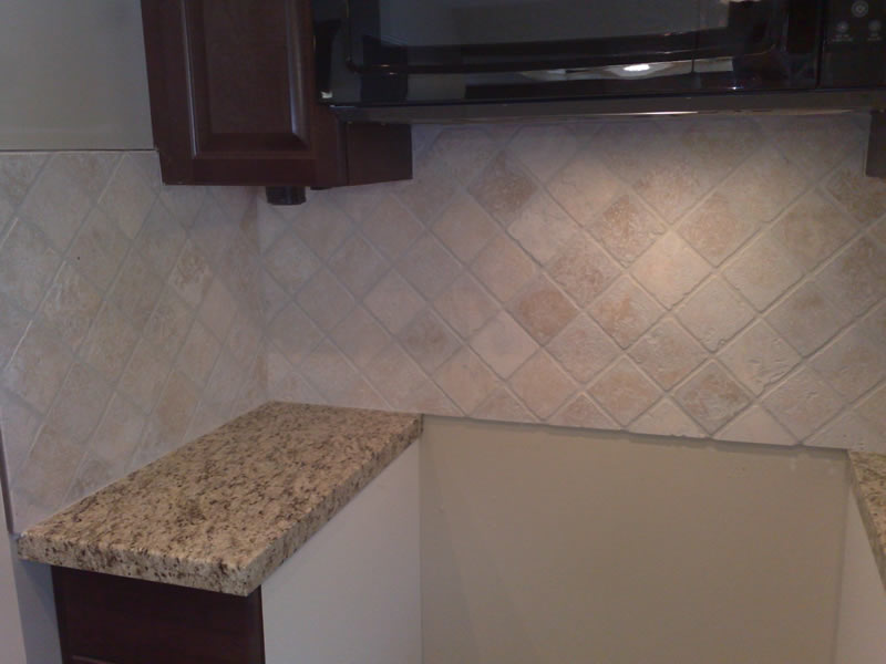 polished granite countertop and diagonal limestone backsplash