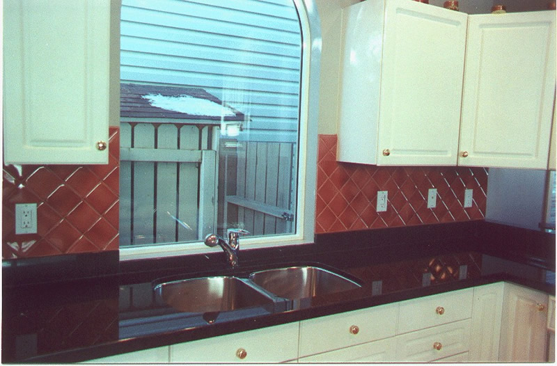 polished black granite kitchen countertop and diagonal tiled backsplash