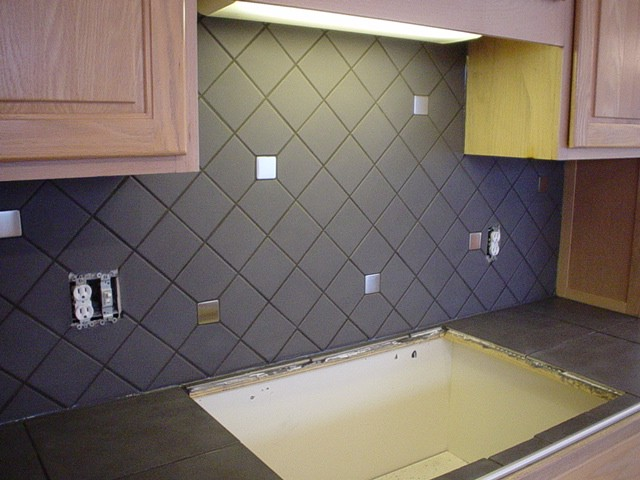 diagonal porcelain backsplash with steel inserts with tiled countertop