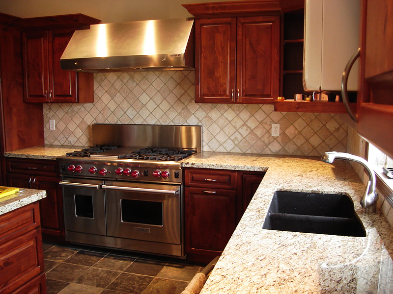 new kitchen with polished granite countertop, slate floor and limestone backsplash
